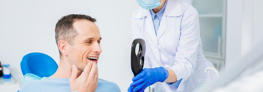 man at dental office admiring new teeth smile