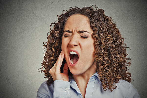 Closeup portrait young woman with sensitive tooth ache crown problem about to cry from pain touching outside mouth with hand isolated grey wall background. Negative emotion facial expression feeling-1