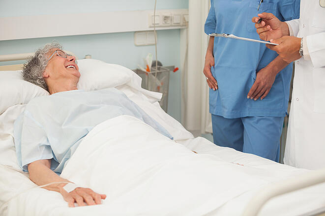 Elderly female patient smiling up at nurse and doctor from hospital bed