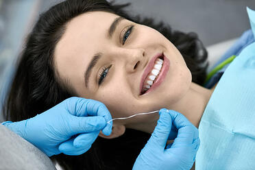 woman flossing at dental office smile
